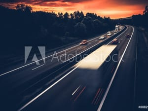 Trucks Driving on Highway at Sunset