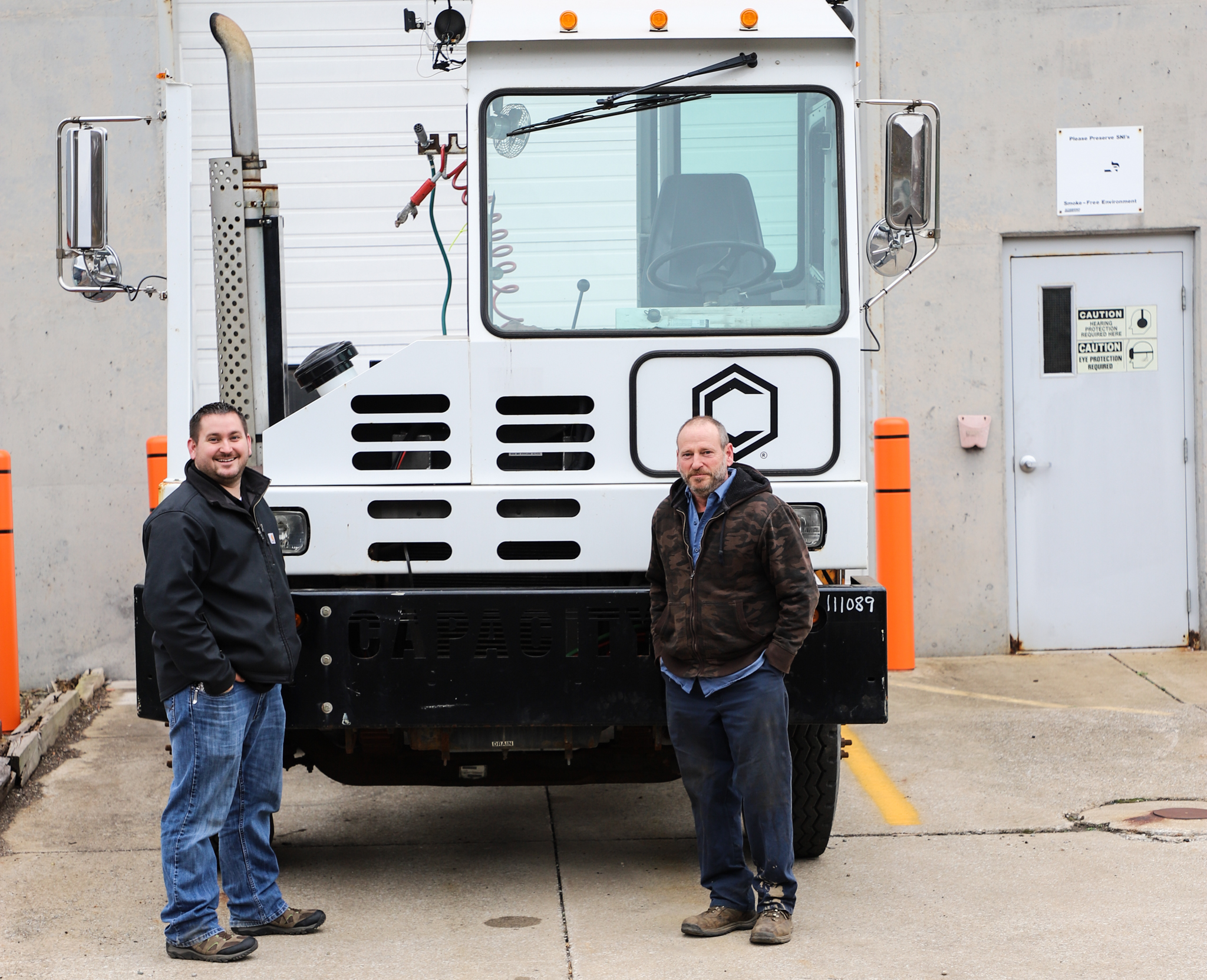 two fleet services professionals standing in front of a semi-truck