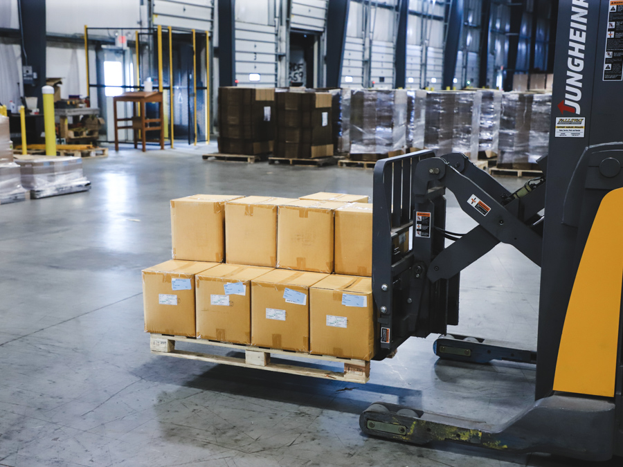 a yellow forklift moving a palette of products across a warehouse